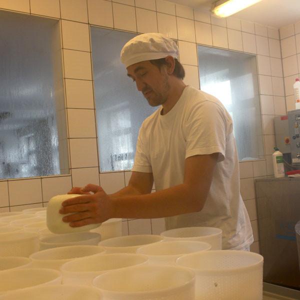 Mann bei der Käseherstellung