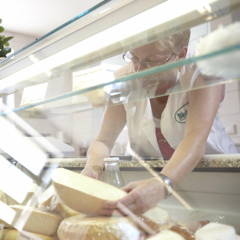 Frau an der Käsetheke im Hofladen