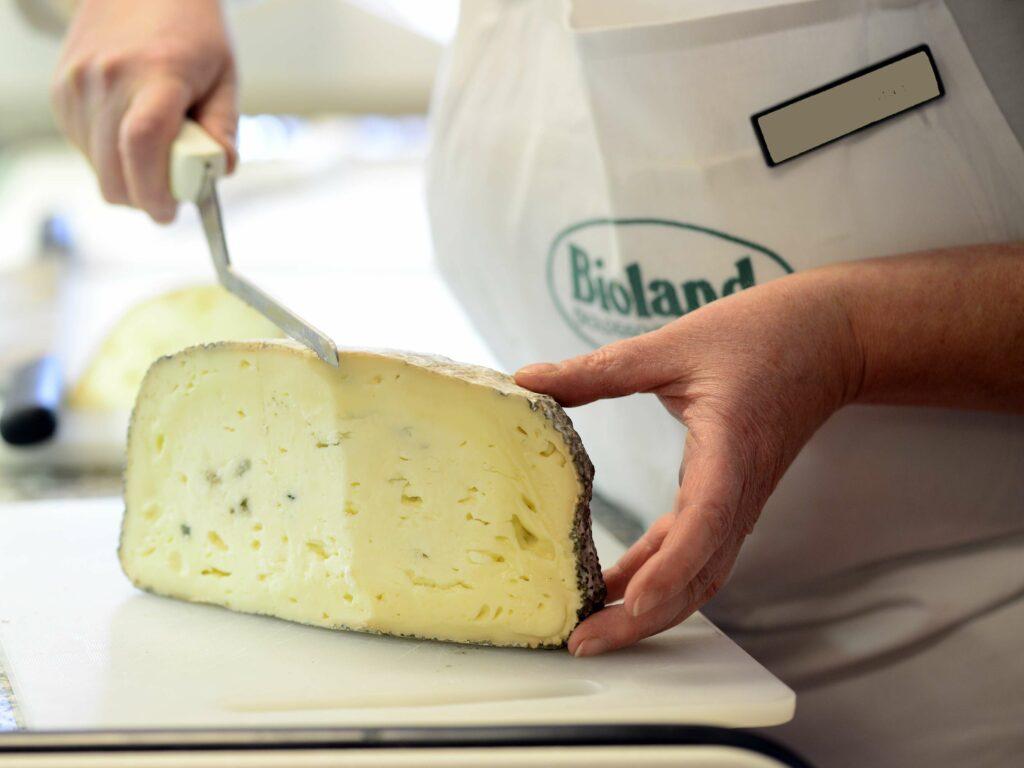 Mitarbeiterin schneidet Käse an